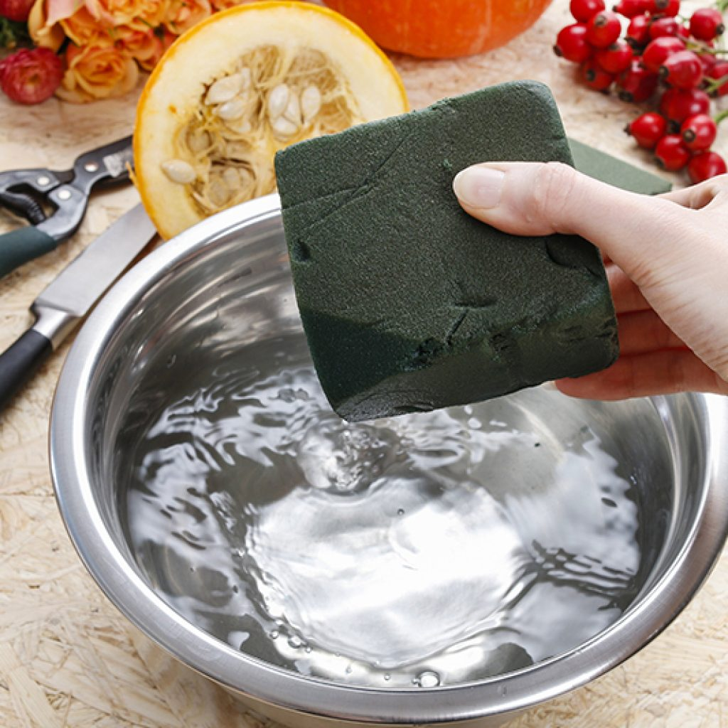 Soaking floral foam to create a Thanksgiving centerpiece