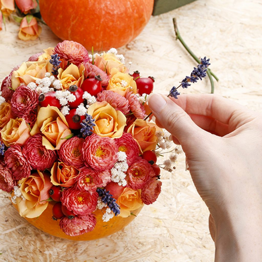 Adding flowers to a pumkin to be used as a Thanksgiving centerpiece