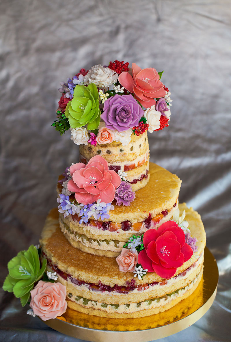 Naked wedding cake with colorful gum paste floral decorations