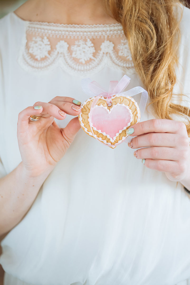 Pretty Pastel Wedding Inspiration - bride holding a heart cookie