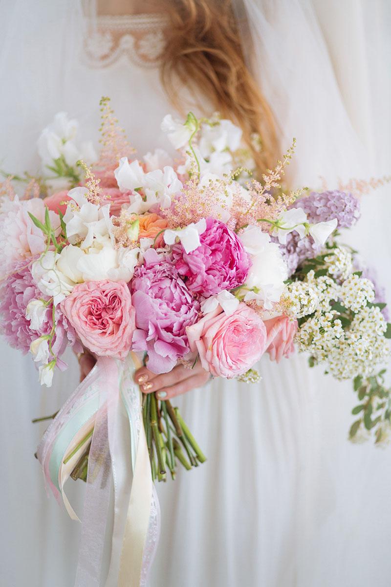 Pretty Pastel Wedding Inspiration - bride holding a pastel bouquet